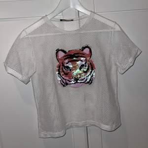 Säljer min T-shirt som har en tiger på med paljetter som man kan dra ner och upp för att ändra färg, jättefin under en långärmad tröja eller vad som helst, använt 1 gång