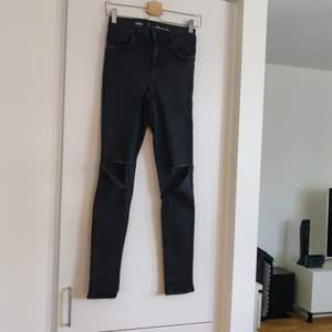 Svarta jeans med hål på knäna. Tajt modell med stretch. Från Bikbok i storlek S. Fraktkostnaden tillkommer.