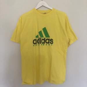Vintage Adidas Equipment tisha från 1990-talet. Tishan är i Gul, grön och svart färg. Väldigt rare t-shirt som ofta inte kommer upp på sidor som Plick. Storlek Large.