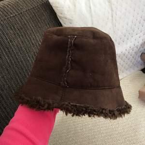En typisk Y2K bucket hat i brun mocka och päls inuti (fake päls såklart!) 🧡✨ Skitcool, storlek M typ och snygg på både vintern o sommaren! Superfint skick, köpt secondhand men aldrig använd av mig 💕