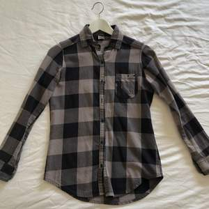 The shirt is made of a fabric that looks like flannel, although i am not sure if it is. It looks in very good condition, but it is missing one button on one of the sleeves (see picture). The fit is not oversized, its just normal. It has been used many times.