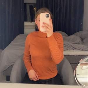 En orange tröja som är polo. Den är ribbad och i jättebra material