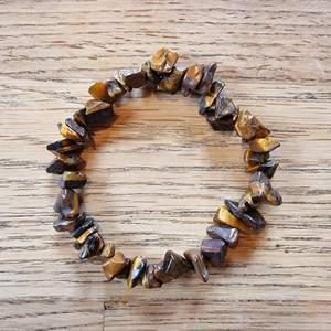 Armband med kristallpärlor av tigeröga. Chipsformade stenar trädda på elastisk tråd. Ca 16 cm omkrets. Skickas i vadderat kuvert via postnord.