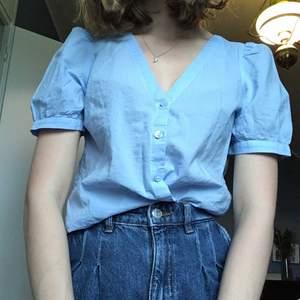 Blå fin blus med puffärmar från Monki. Den är v-ringad framtill med knapp knäppning. Jag har näst intill aldrig använt den, så den är så gott som ny☺️