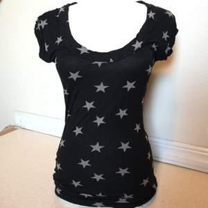 En tröja ifrån Bikbok full av stjärnor och med en djup urringning som sitter fint på kroppen. Använd endast enstaka gång.