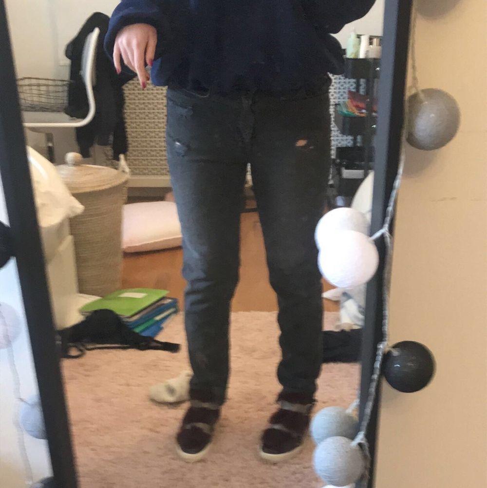 Ascoola gråsvarta jeans med slitningar. Använda 3 gånger. Säljer pga har ett annat par liknande🖤🖤 Storleken är 40 och jag brukar ha 36-38, men dem sitter lite pösigt på mig. Skulle säga att de passar 36-40 beroende på hur man vill att dem ska sitta✨ De är highwaisted men jag har på mig dem kågmidjade på bilden. Kontakta privat om du är intresserad🖤✨🖤. Jeans & Byxor.