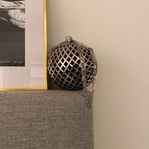 En klotformad aftonväska i marinblått sammet och silverdetaljer. Kedjan som medföljer kan justeras. Super fin väska som kan användas till middag,fester, bal, bröllop, nyårsfest m.m. I topp skick, då den endast är använd en gång.