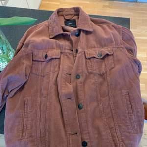 Manchester. Ganska tunn men funkar som en sen vår/ sommarjacka eller som en skjorta.  Jag har klippt av den, på mig går den till svanskotan och jag är 177 cm.
