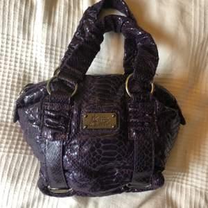 Jättecool lila färg med krokodil-mönster. Mindre väska men man får plats med mycket och kan bäras på axeln. Köpt secondhand, knappt använt så i bra skick!💕💞 Priset är exl frakt