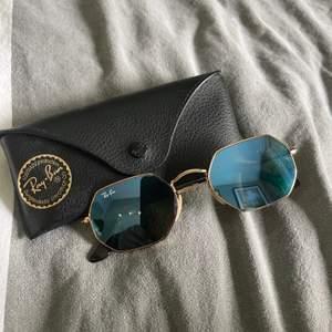 Säljer ett par oanvända Ray-Ban solglasögon i hexagon form och gulddetaljer. Glaset är tonat glas i blåfärg. Nypris: 1800kr
