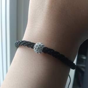 Svart flätat armband med silvrig pärla på. Använd fåtal gånger. Justerbara band och passar därför alla storlekar!