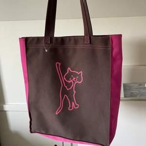 Brun/ rosa vintage tygväska i toppskick! 💘 Passar till precis allt och färgerna gör att det blir en 2000s vibe samt look!! Riktigt unik och cool, med en katt på. Finns dragkedja både bak och inuti. Väskan själv stängs också mha en dragkedja.