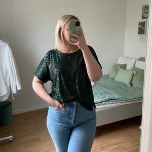Super fin mörk grön T-shirt från H&M med paljetter! Perfekt till fest eller att glittra till en vardags outfit! ALDRIG använd så i utmärkt skick!