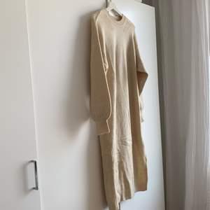 Stickad klänning med rundad hals och slits nedtill. Aldrig använd, endast testad.