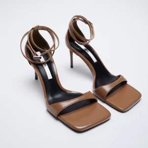 Oanvända rem-sandaletter med snörning från Zara. Brunt skinn. Fyrkantig, öppen tå. Klackhöjd 7,5cm. Sportsula med skum av latex för bekväm komfort. Knäppning med spänne på vristbandet. Ord.pris 399.-