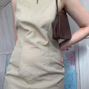 Retro klänning som är randig i vitt och beige🤎 Lång men nästan osynlig dragkedja i ryggen🤎 Fin att matcha med ett bälte eller andra accessoarer🤎 Kan skicka med frimärken för att få ner fraktkostnad🤎