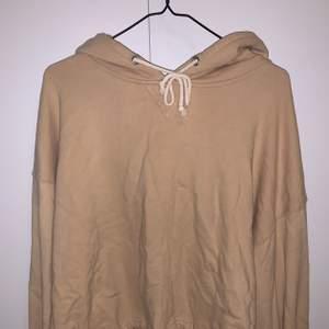 En beige hoodie från Bik Bok som knyts där nere.