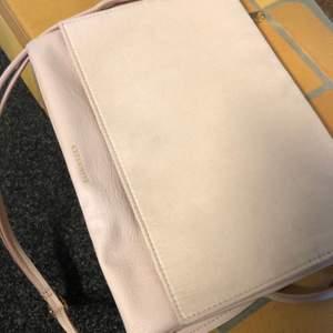 Ljusrosa väska i mockaimitation på framsidan och läderimitation på baksidan. Använd fåtal gånger. Kan bäras både som axelremsväska eller som kuvertväska.