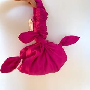 Rosa tygväska med knytar. Skickar gärna mer bilder. Möts upp i Stockholm alt står köparen för frakten.