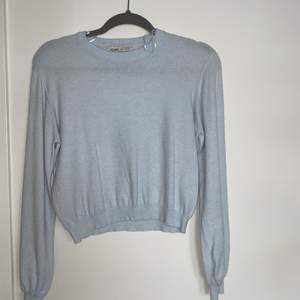 Finstickad ljusblå tröja. Lite kortare i modellen.