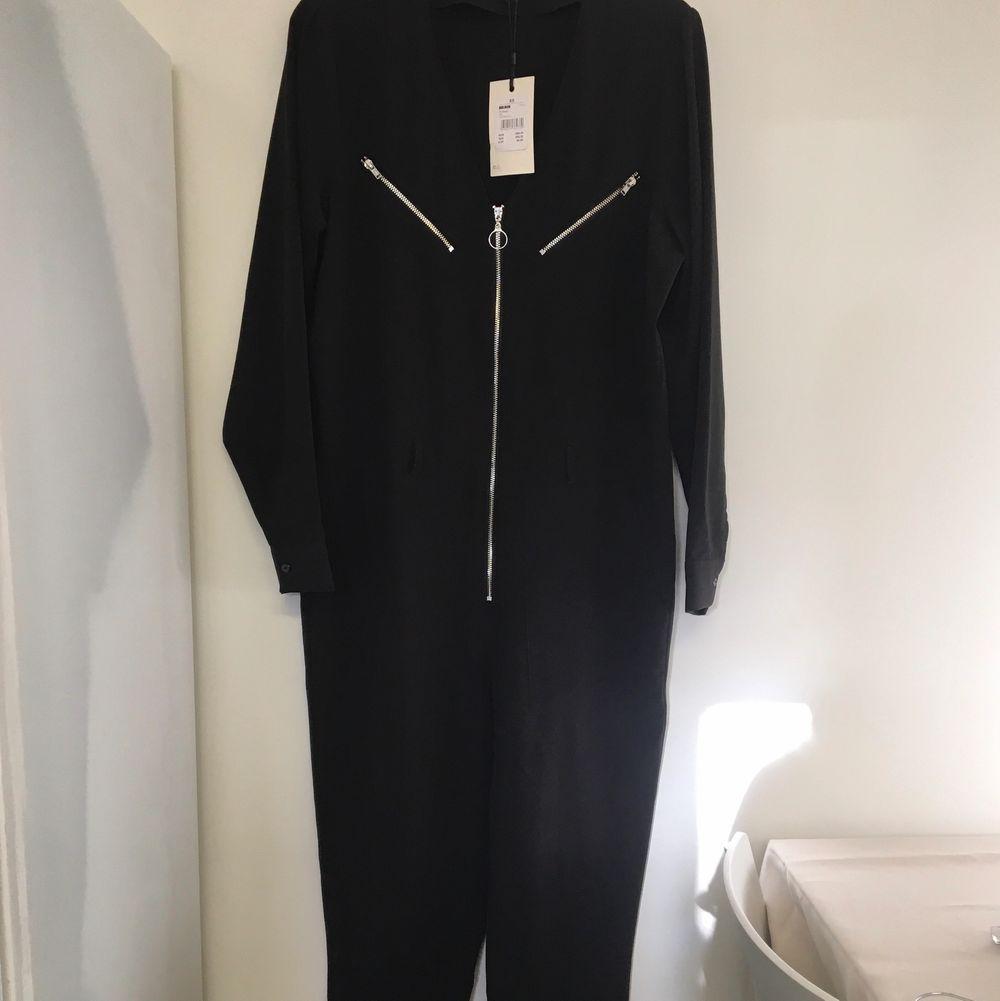 Svart jumpsuit med dekorativa dragkedjor och skärp i midjan. (skärp ej med på bild) Köpt från Bikbok för 499kr och aldrig kommit till användning. Lappar kvar. Om många är intresserade blir det budgivning. Storlek XS men passar S också. . Klänningar.