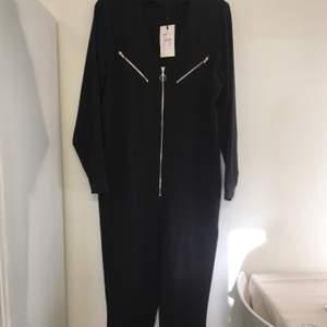 Svart jumpsuit med dekorativa dragkedjor och skärp i midjan. (skärp ej med på bild) Köpt från Bikbok för 499kr och aldrig kommit till användning. Lappar kvar. Om många är intresserade blir det budgivning. Storlek XS men passar S också.