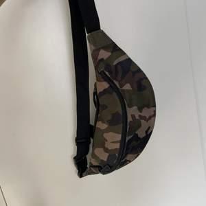 """Militärfärgad bunbag, går att använda som """"handväska"""". Ser inte ut som den """"typiska"""" bunbagen och har extremt mycket förvaring."""