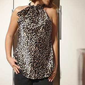 Halterneck topp, leopardmönster. Knuts vid halsen. Stor i storleken men formbar. Polyester.