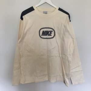 Vintage Nike Longsleeve i storlek XL. Den har en väldigt vårig pastellgul färg. Skulle se väldigt fin ut matchat med ett par blåa jeans. Vintage skick med inga defekter.