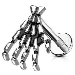 ALDRIG ANVÄND pga felköp!  Smycke med skeletthand, funkar till piercing i öra som örhänge, eller till läppiercing! Labretstav i kirurgiskt stål, handen är i mässing.  Kan skicka bild på förfrågan :)