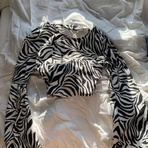 Supersnygg kort zebra tröja, med långa flared armar och en öppen rygg. Använd bara ett fåtal gånger. Köpare står för frakten! 💛🌼💛🌼