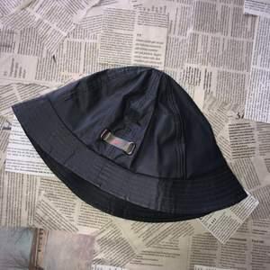 Riktigt cool buckethat i ett galoonliknande material (regntät) i mörkgrått med ett oranget swooshmärke, använd fåtal ggr