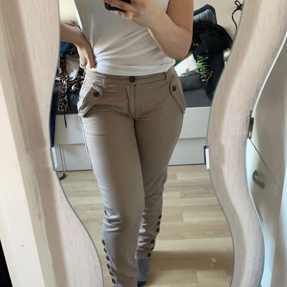 Skit snygga oanvända beiga byxor i str 34. Jätte fina knappar på och sitter snyggt vid röven. . Jeans & Byxor.