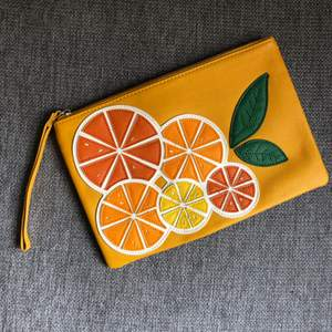 Orange clutch with tasty orange decoration from Mango. Make your outfit special!