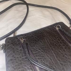"""Söt liten grå väska med långt band. Fina drsgkedjs detaljer i fram. Typ """"krokodil mönster"""" i tyget. Säljs då den inte används. Går att ta bort bandet!"""