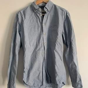 Blå grå skjorta med lite svarta märken på sig. Slimfit från Dressman, i storlek S. Knappt använd då jag upptäckte att jag inte passar i blått och att den nu är alldeles för liten för mig runt bysten