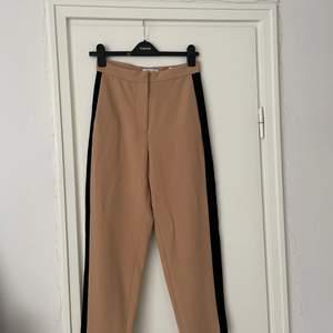Beiga kostymbyxor med svarta ränder på sidorna. Använda ett fåtal gånger!