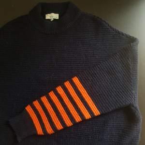 Fin stickad tröja i mörk marinblå med orangea detaljer. Inte använt alls och är i fin skick.