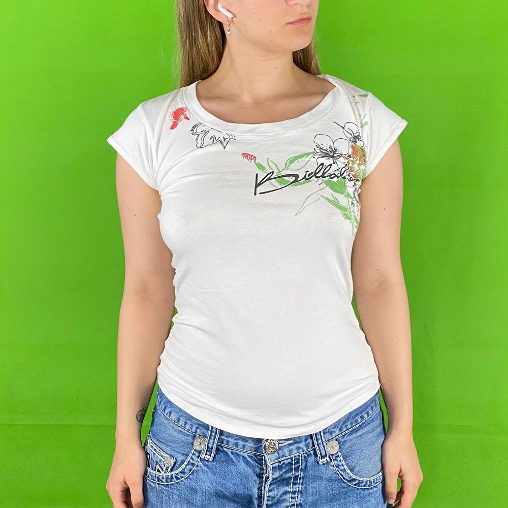 Y2K billabong t-shirt med hibiskusblommor runt loggan och bakom. I bra skick. Står storlek XL men är mindre i storlek. Modellen använder S och är 169cm för referens. Mått finns nedanför. Materiallapp har suddats ut men t-shirten är stretchigt. Spårbar frakt på 66kr är inräknad i priset. Axel till axel 38cm. Arm längd 7cm. Byst bredd 43cm. Axel och ner 59cm.. T-shirts.