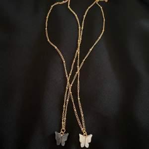 Två fina helt nya fjärilshalsband. Använder inte guld längre och därför säljer jag dem. Det ena halsbandet är med en svartgrå fjäril och det andra är med en pärlvit fjäril. Priset är per halsband.