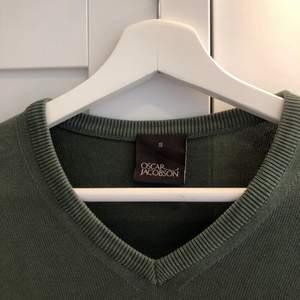 Stickad tröja i grön matt färg från Oscar Jacobsson. Lätt V-ringad krage. Has med fördel över skjorta och kostymbyxor. Välanvänd men i fint skick. Nypris 1300 kronor.