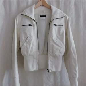 En retro vit skinnjacka som är rätt kort men passar bra till både låga och höga jeans