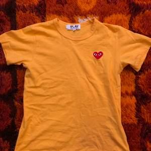 Säljer denna jättefina brandgula tshirt från Comme des Garcons! Väldigt fint skick, kommer tyvärr aldrig till användning. Storlek M. Går att mötas upp i Hagfors eller så skickas den med posten där köparen står för frakten!