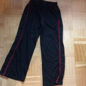 Oanvända! Säljes pga för långa (är 1,54) Skönt material! Trendiga & bekväma sweatpants med fickor frampå, knappar längs sidorna & vida nertill. Helsvarta, förutom den röda randen. Inga hål eller andra skavanker!