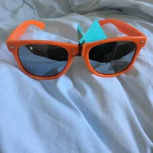 Ett par orangea solglasögon från Wannabes. Helt nya. Frakt ej inkluderat