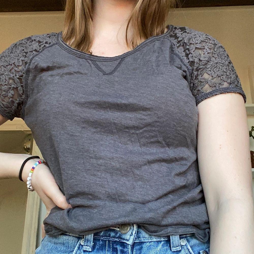Mörkgrå tshirt i skönt material med spets baktill. Använd men fint skick. Small.. T-shirts.