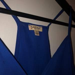 Ett blått blus linne. Made in USA med SIZE S. Lite längre baktill med fin V ringning.