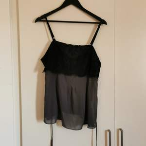 A top with a black lace up top, otherwise a chiffon fabric. Satin string to show off the waist or bust, can be tied in the back too. Flowy and beautiful. Adjustable straps. Sits well over the bust (although maybe a B cup would be perfect) zipper at the side. I have a C cup and can just fit into a uniboob 🤭 used once.