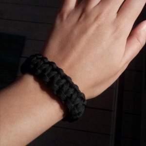 Detta är ett svart paracord armband som jag själv har tillverkat. Armbandet är 20 centimeter långt och passar alla oavsett kön!