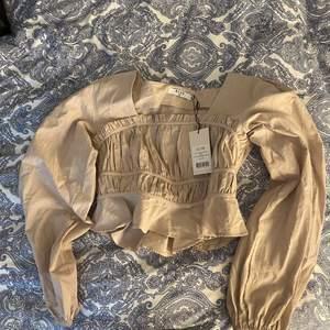 En jättefin beige blus från Na-kd, den är oanvänd, storlek EU 36. Köpt för 399kr, säljer nu för 200kr. Köparen står för frakten (återkommer med fraktpriset när den ska skickas)💓